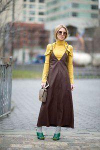 Сукня без рукавів коричневого кольору, расклешенной моделі, довжиною максі поєднується з тонким светром жовтого відтінку.